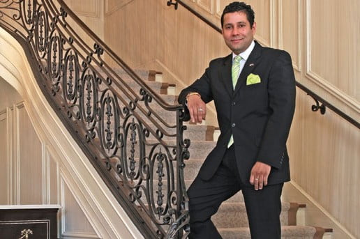 Ambassador Neil Parsan stands at the bottom of the formal staircase leading up to the second floor of the embassy.