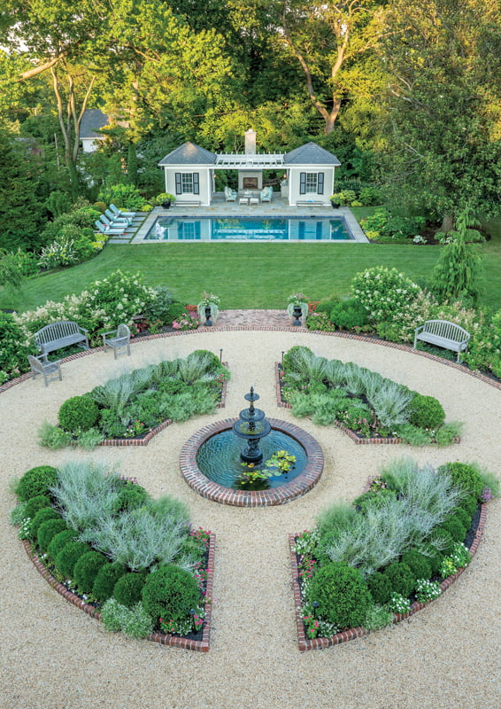 The formal flower garden features a fountain as a centerpiece.