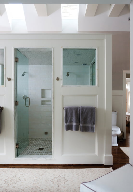 The shower enclosure  is paneled to echo the home's architecture.