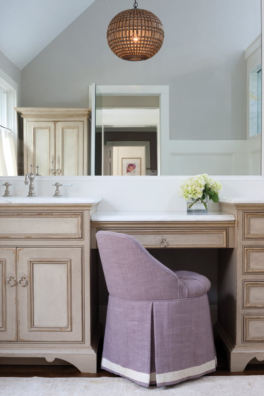 The custom vanity seat is upholstered in stain-treated linen.