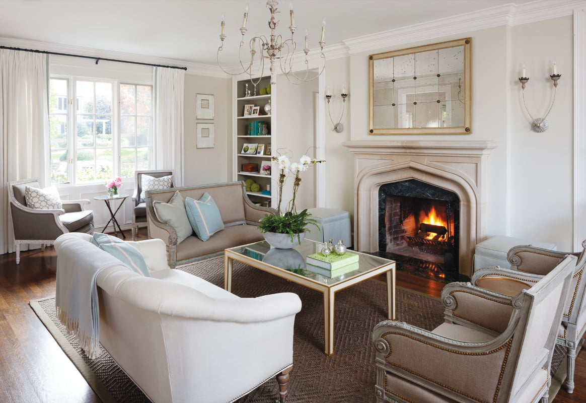Focused on the original limestone fireplace, the living room includes armchairs and a settée purchased in Paris.