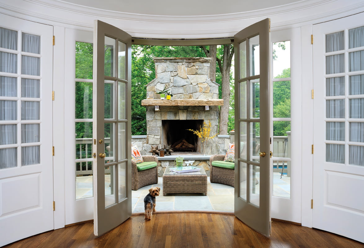 French doors open to a terrace with a new stone fireplace and outdoor furniture by Kingsley-Bate.