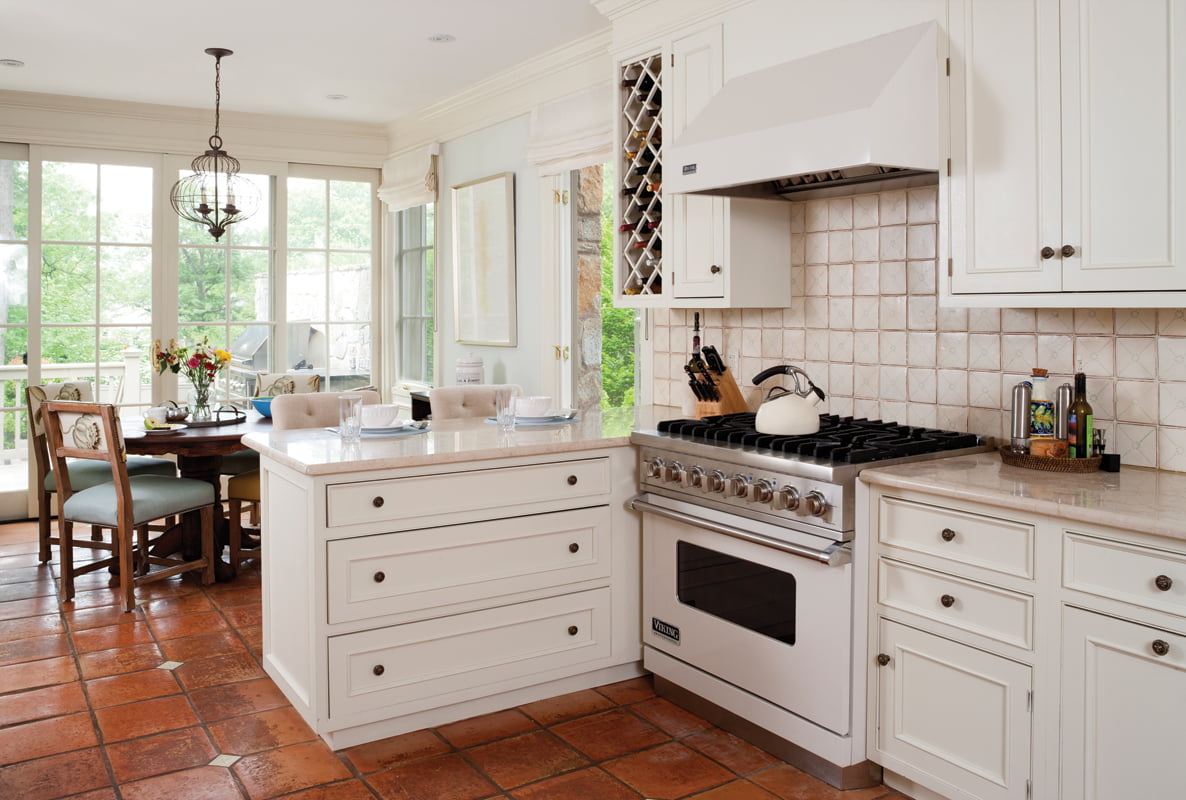 The kitchen was refreshed with marble countertops and a backsplash of hand-painted tiles from Walker-Zanger.