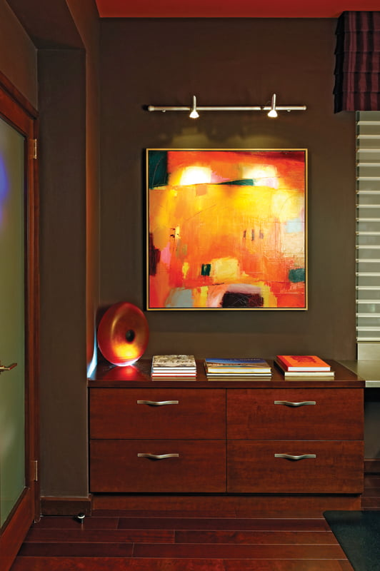 An orange palette prevails in the office, featuring a painting by Carolyn Cole.
