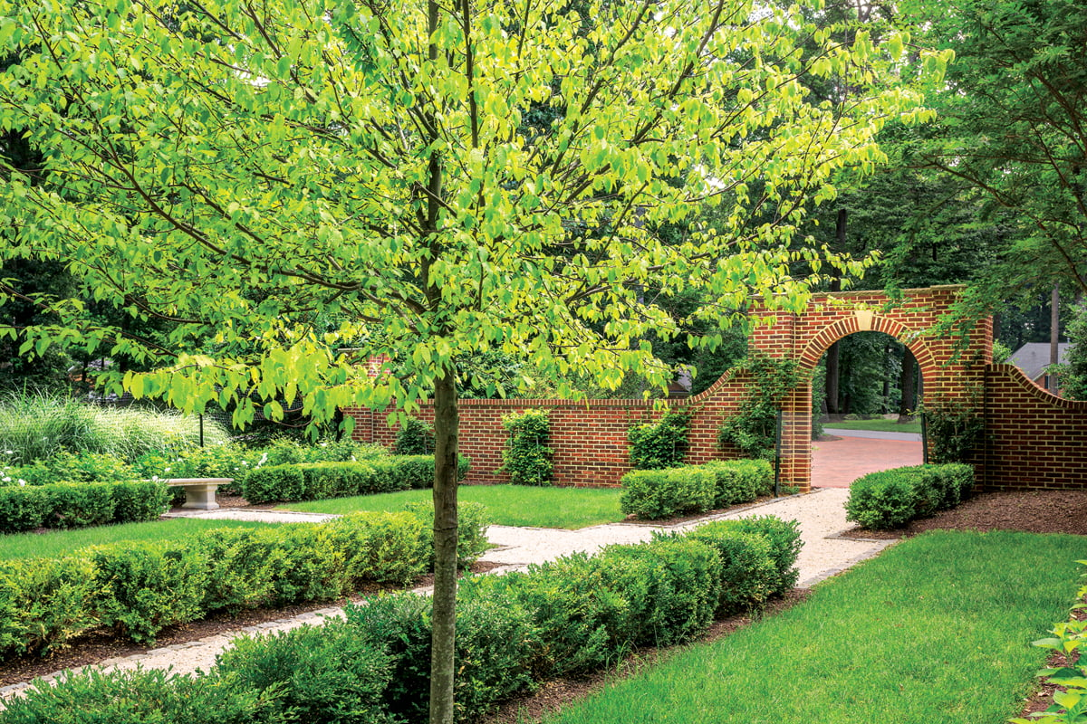 The archway—a replica of one found at Mount Vernon—is anchored to the landscape by a matching wall.