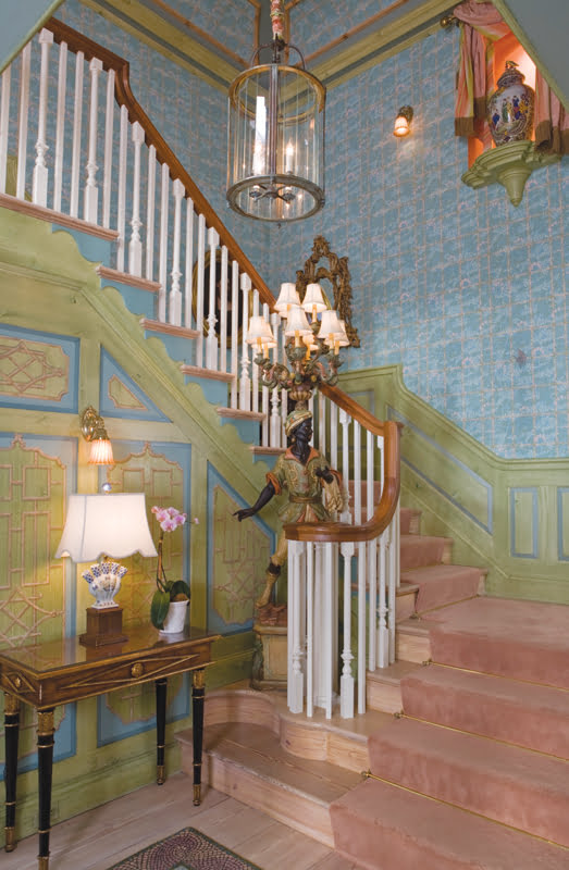 A grand, two-story foyer features handmade paneling faux painted to match the wallpaper.