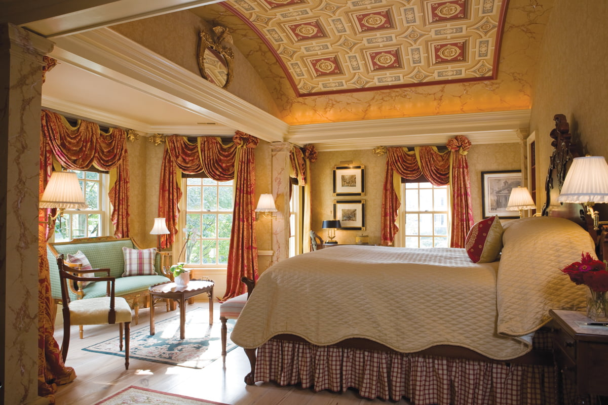 The master bedroom boasts a barrel-vaulted ceiling covered in Scalamandré wallpaper.