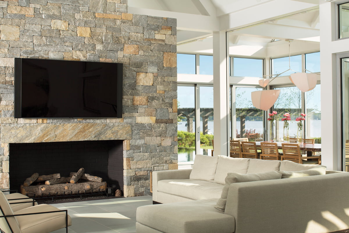 In the great room, a massive stone chimney houses a fireplace and flat-screen TV.