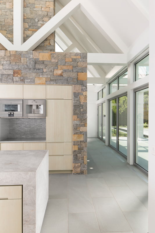 Kitchen cabinetry and appliances are housed on the other side of the massive stone chimney.
