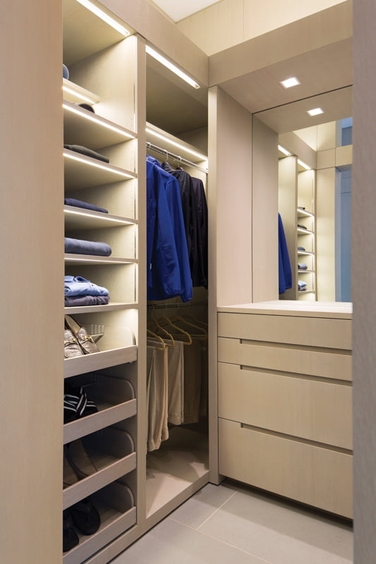 In the master suite, custom cabinetry streamlines storage in the closet.