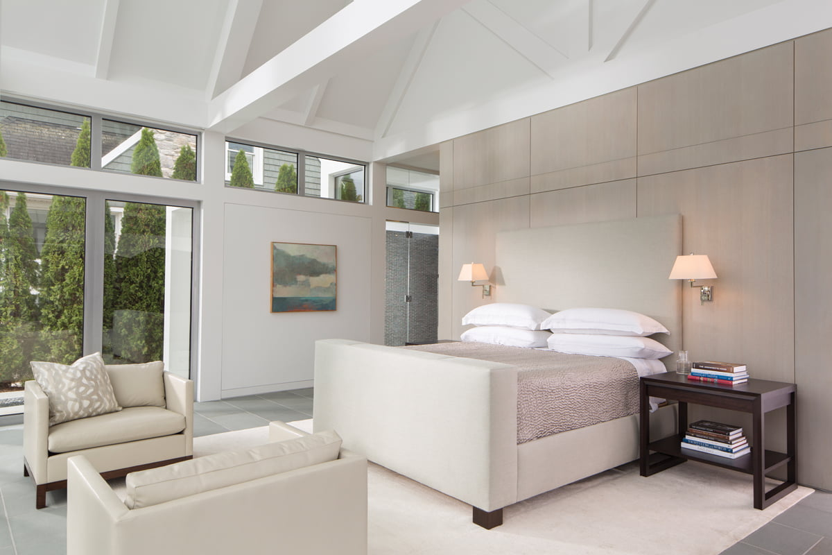 The restful master bedroom overlooks the river while a remote raises and lowers hidden window shades.