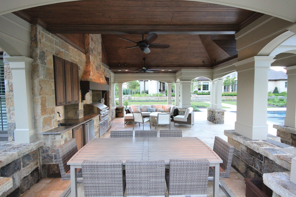 The Pool House Contains A Sitting Area And Kitchen With Stone Range Hood