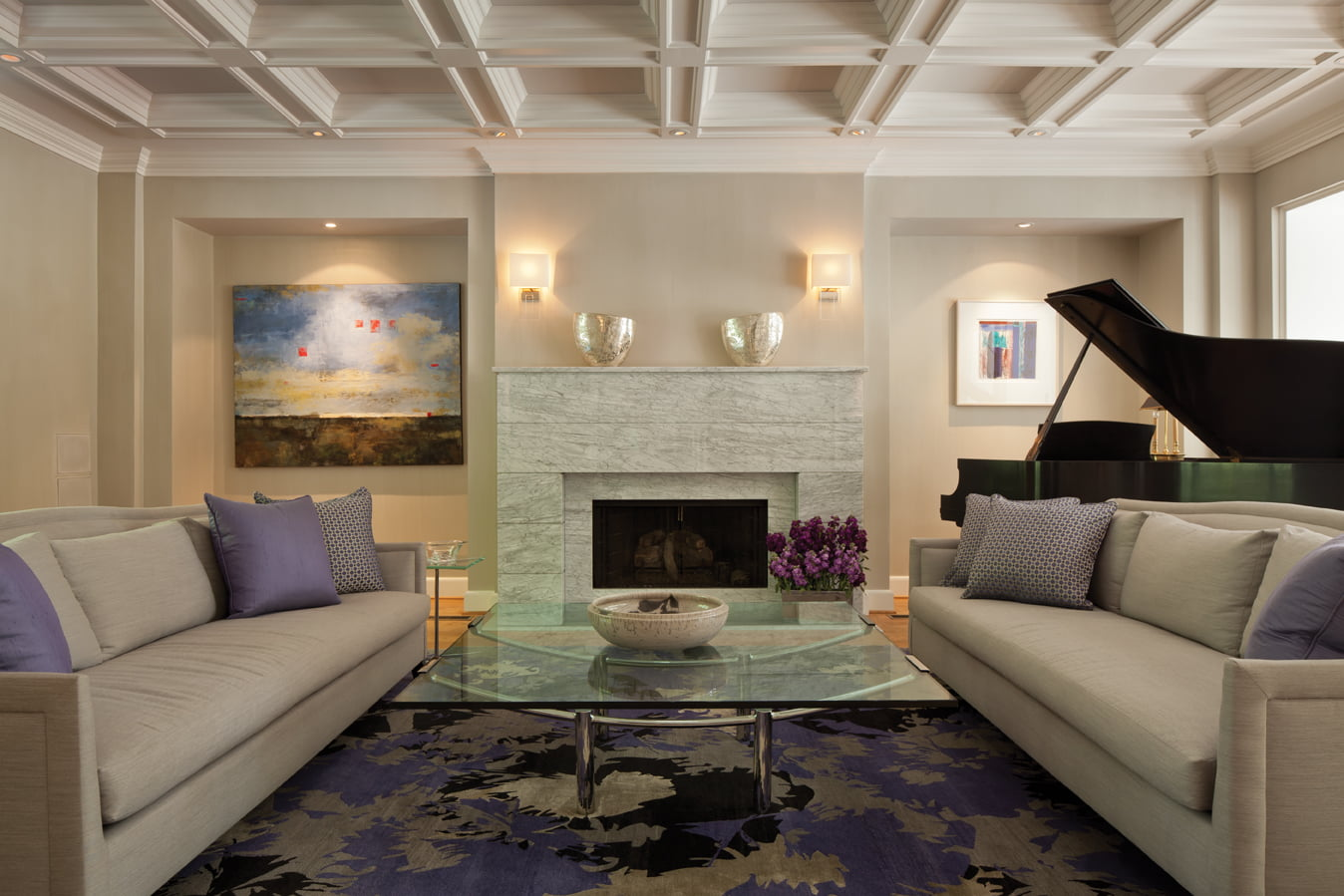 In the sunken living room, sofas by Donghia and a  marble fireplace surround reflect a lighter, pared-down style.