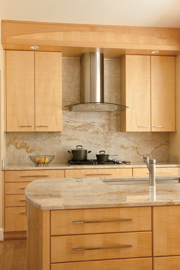 Vallon paired Tiger's Eye maple cabinets with marble-like granite countertops.