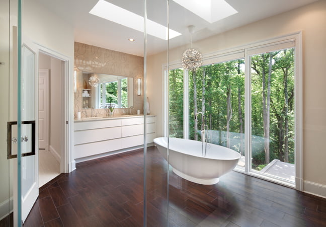 Floor-to-ceiling windows bring the outdoors in, while a soaking tub offers a bird's-eye view.