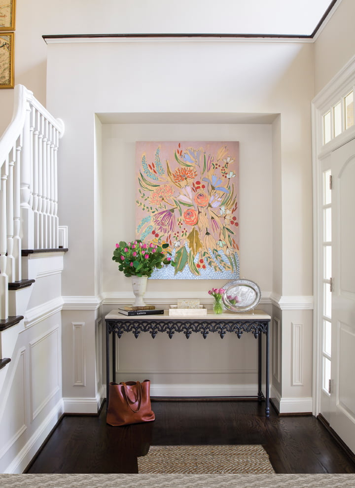 A limestone-topped console by Hollis & Knight occupies the foyer below a painting by Lulie Wallace.