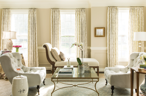 In the sitting room, floral curtains by Jane Churchill and a glass-topped coffee table by Salvations keep things airy.