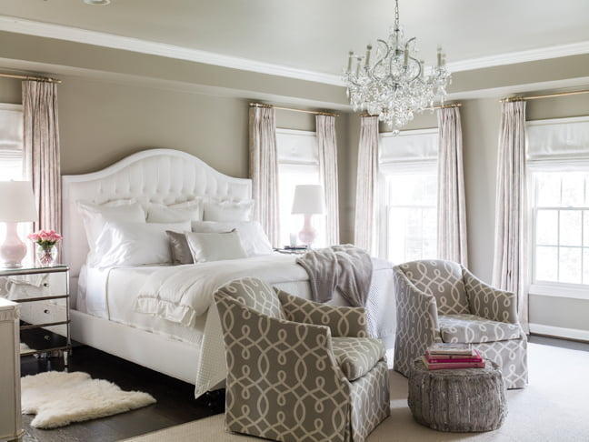 In the master suite, chests by Currey & Company flank a tufted bedstead by Lee Industries.