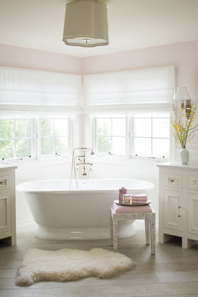 The bathroom features a graceful soaking tub by Victoria + Albert.