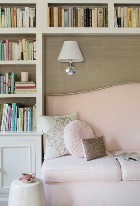 A grasscloth wall covering by Phillip Jeffries provides a backdrop for a daybed.