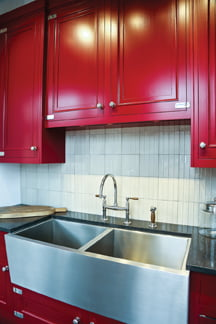 The collection includes richly painted kitchen cabinets and stainless-steel sinks.