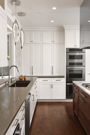 Painted Shaker-style cabinetry is topped with black Caesarstone counters.