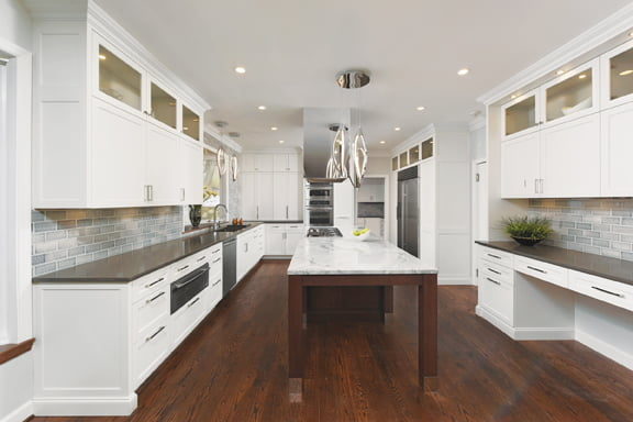 A long island is stained with an oiled-walnut finish and topped with White Fantasy granite.