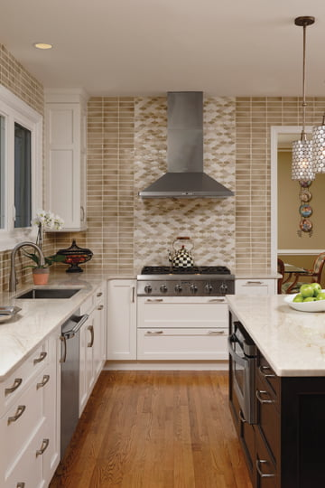 A backsplash of Encore custom-blended mosaic tile in a fence pattern creates a focal point above the cooktop.
