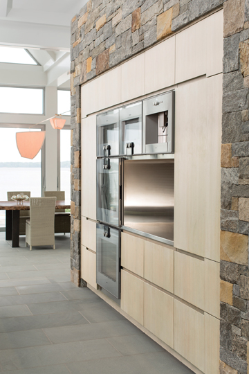 Appliances are built into a massive stone wall.