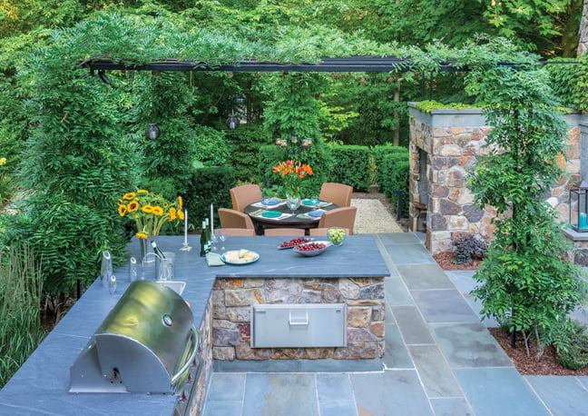 The outdoor kitchen is equipped with a grill and storage drawer.