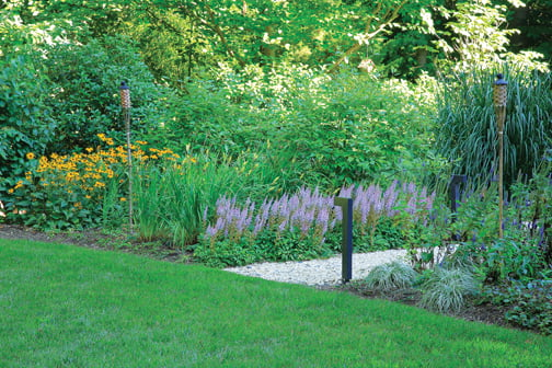 A pea gravel path leads to a secluded play lawn.
