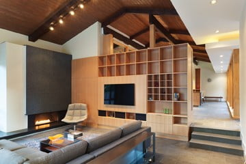 The original wood-paneled ceiling extends to the family room with its granite-faced fireplace.