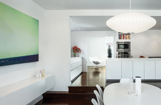 The dining area houses a Piet Hein table, Eames chairs and a BoConcept cabinet along the wall.