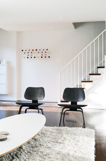 In the existing space,  a colorful decorative piece by Eames hangs on a wall near the stairs.