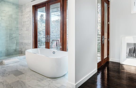 Greer designed an open master bath with a sculptural soaking tub and glass-enclosed shower.