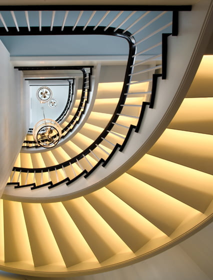 LED lights concealed on the underside of the stair treads illuminate the four-story staircase.