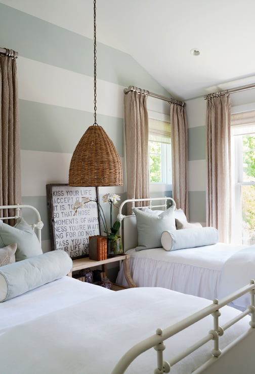 Twin beds from Restoration Hardware occupy a room painted with broad stripes.