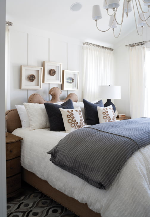 A white-paneled bedroom boasts a bed from Noir Furniture and a hide rug by Surya.