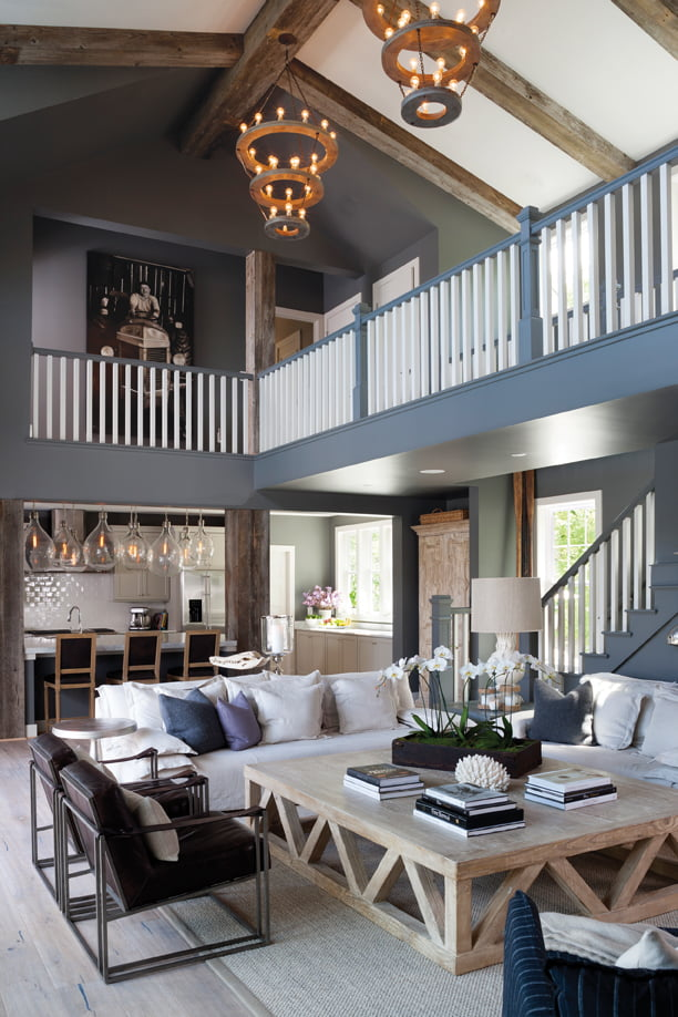The great room offers plenty of seating around  a massive custom coffee table; beyond is the kitchen.