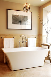 In the bathroom of a DC Colonial,  traditional travertine floors mix with a contemporary tub.