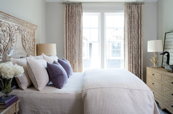 In one guest room, Evans selected a carved bedstead from Classic Home to pick up the hue of the Osborne & Little draperies.