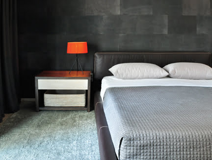 In the bedroom, a suede-paneled wall creates a dark and cozy backdrop.