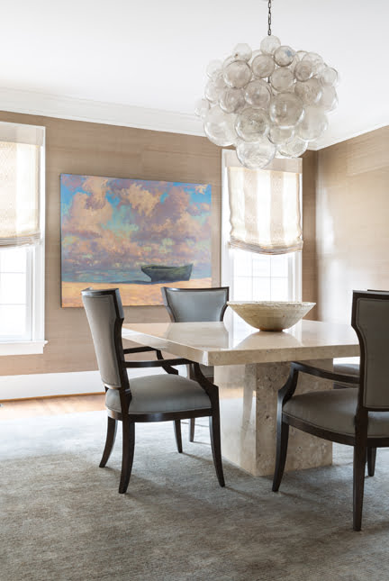 Bronze grasscloth adorns a dining room featuring a table from Nest and a chandelier by Oly.