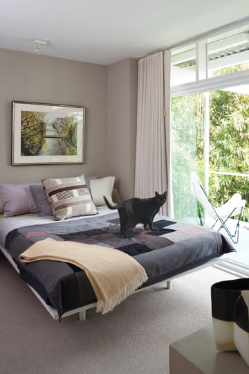 In a departure from white, a guest bedroom features a moodier shade.