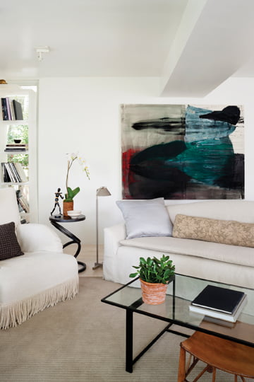 An abstract painting by Simon Wells hangs above the living room sofa.