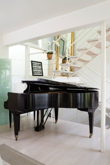 A sleek baby grand piano provides a contrast to bleached-oak floors.