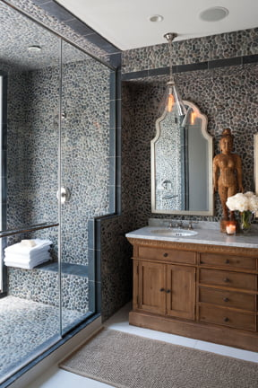 In the master bath, river-rock tile clads the wall and shower, where a door opens to a sheltered outdoor niche.