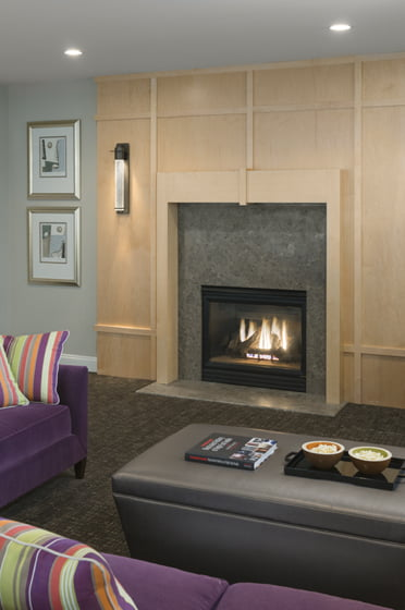 The exaggerated height of the mantel adds presence to a fireplace framed in limestone and custom maple panels.