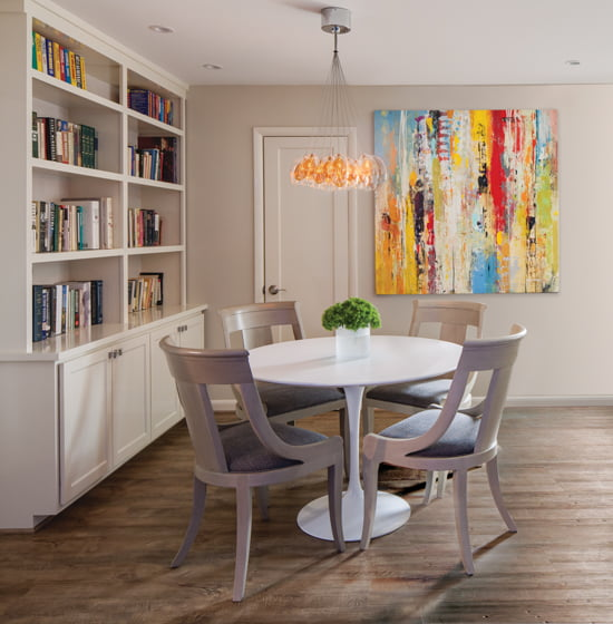 A small space for playing games or enjoying casual meals gets its big style from a Saarinen Tulip Table, bold abstract artwork and a modern chandelier.