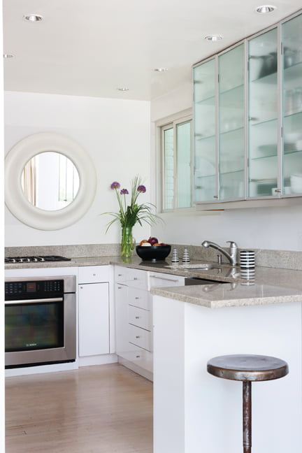 The modern kitchen features glossy laminate and glass-fronted cabinets.